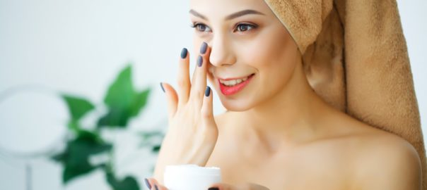 beautiful woman using a skin care product