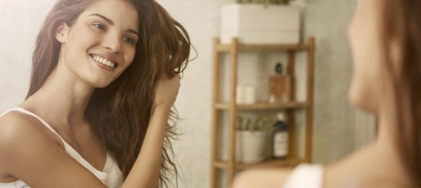 Girl touching her hair and smiling while looking in the mirror