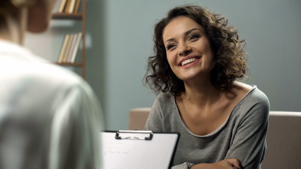 Young happy lady talking with psychologist at clinic