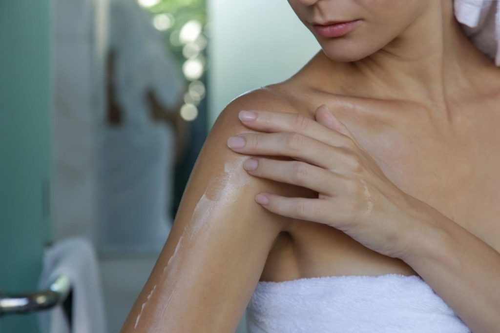 Woman applying body cream to moisturize her skin after shower