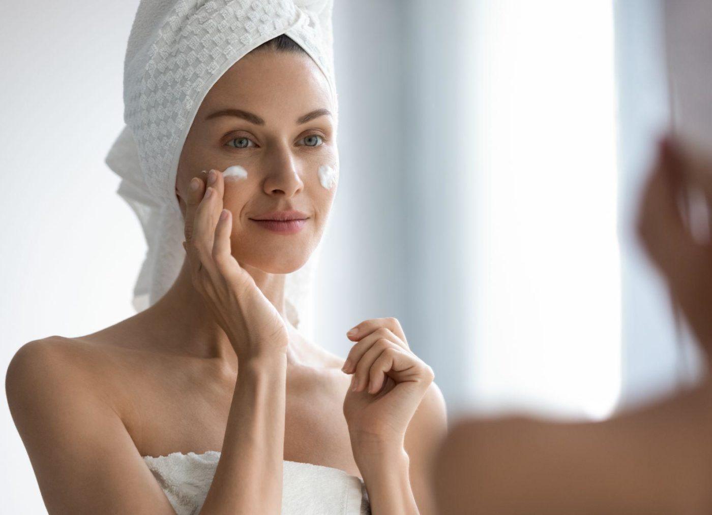 Attractive young adult woman apply facial cream look in mirror